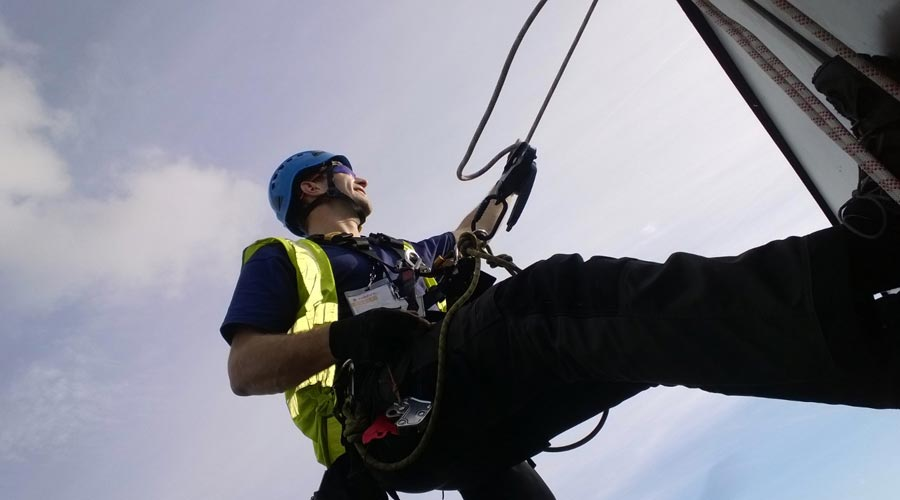 Engineer abseiling to check fabric structure